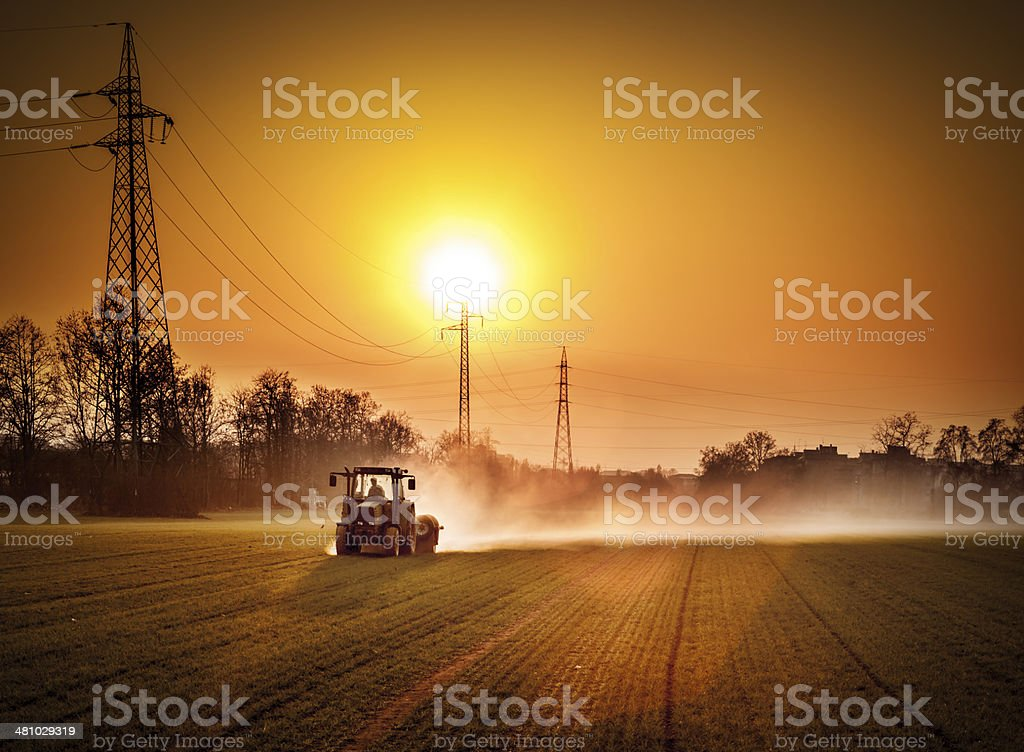 Tractor In A Field At Sunset stock photo
