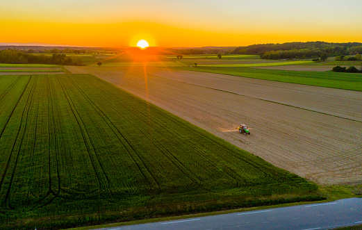 Aerial view of idyllic rural landscape with tractor in field at sunrise