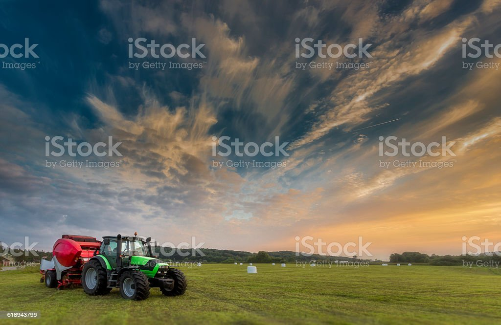 Tractor in sunset light with ensilage balls in background stock photo