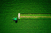 Tractor mowing green field, aerial view.