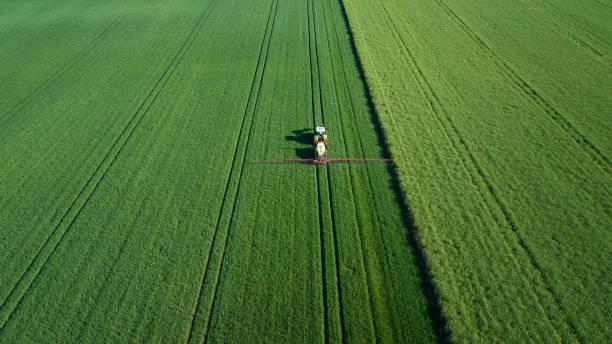Traktor auf einem Weizenfeld im Frühjahr - Luftbild – Foto