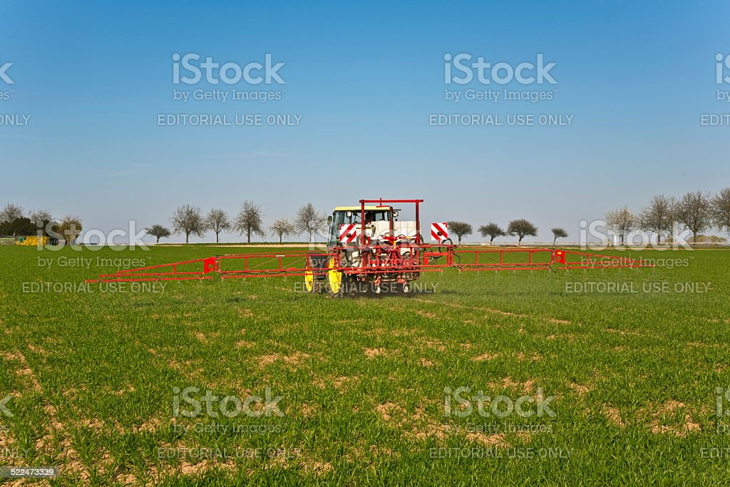tractor on field sputtering pest protection stock photo