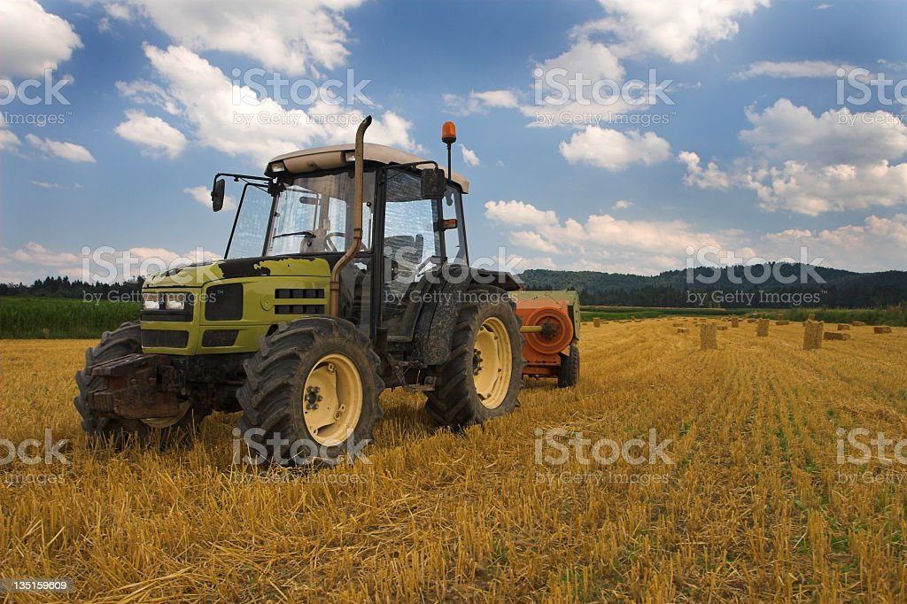 Tractor on harvested wheat field royalty-free stock photo