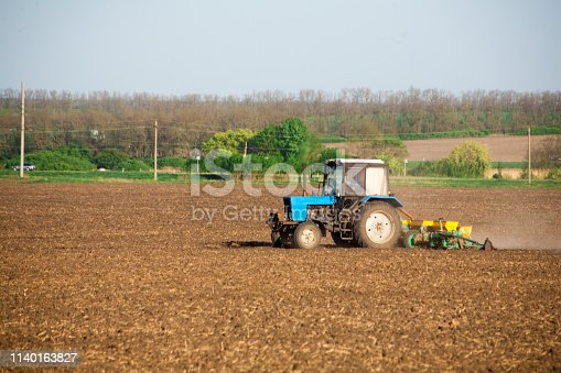 Agricultural tractor rides across the field with a seed drill spreading mineral fertilizers