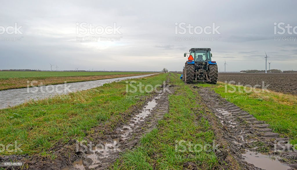 Tractor parked along a canal in winter stock photo