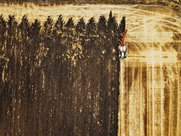 Tractor plowing a field Aerial view of agriculture fields monoculture stock pictures, royalty-free photos & images
