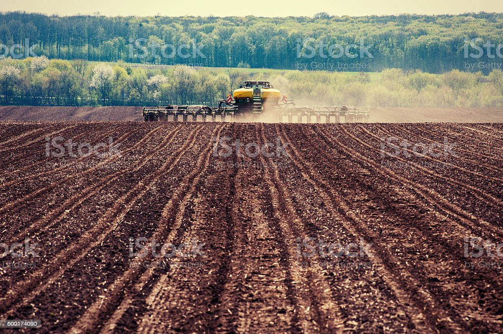 Tractor plowing farm field in preparation for spring planting. stock photo