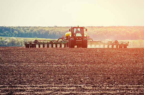 Tractor plowing farm field in preparation for spring planting. Tractor plowing farm field in preparation for spring planting. garden hoe stock pictures, royalty-free photos & images