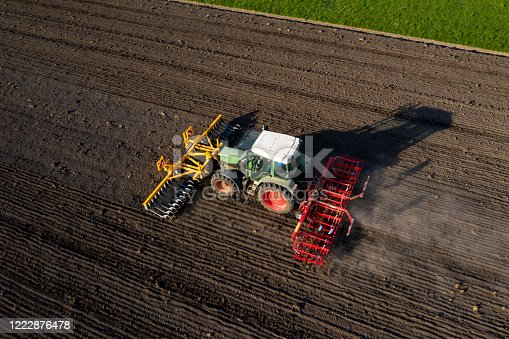The tractor plows a field, aerial view.