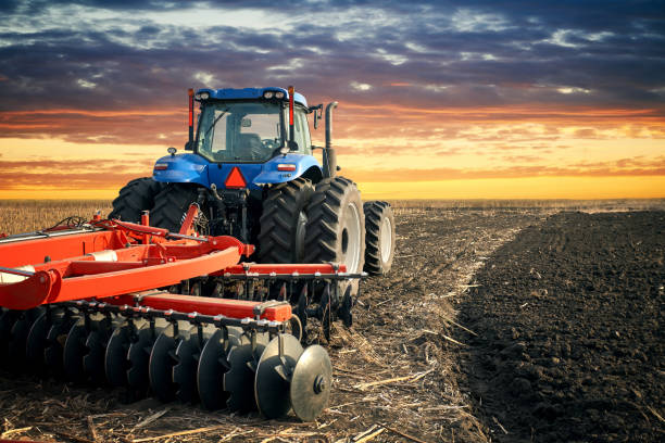 Tractor plowing field on sunset background stock photo