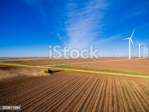 892160114 istock photo Tractor plowing field with wind turbinel farm in the distance 520611594