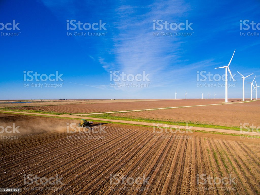 Tractor plowing field with wind turbinel farm in the distance stock photo
