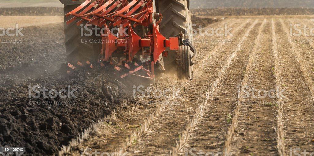 Tractor plowing fields  -preparing land for sowing royalty-free stock photo