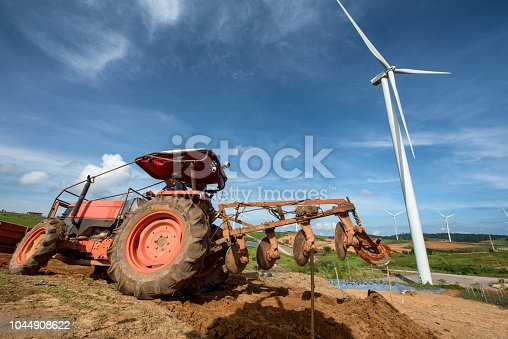 Tractor plowing in plantation farm with wind turbines clean energy electricity.