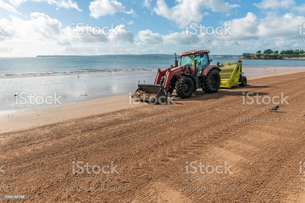 Tractor rakes sand on the beach in Torquay, Devon stock photo