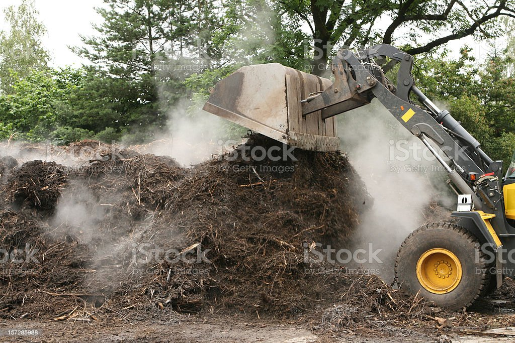 Tractor rearranging compost royalty-free stock photo