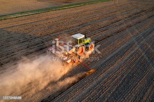 Tractor drilling seed in plowed field, aerial view.