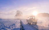 istock Tractor silhouette through fog, on snowy field 503156044