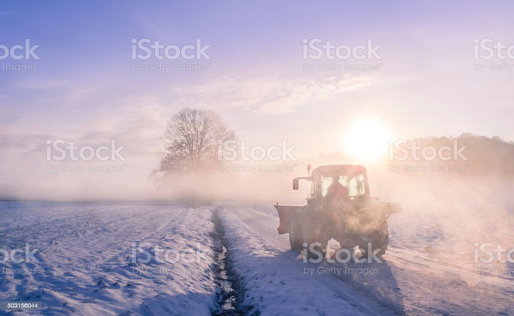 Tractor silhouette through fog, on snowy field stock photo