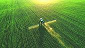 istock Tractor spray fertilizer on green field. 1249522339