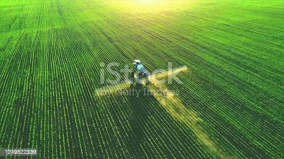 istock Tractor spray fertilizer on green field. 1249522339