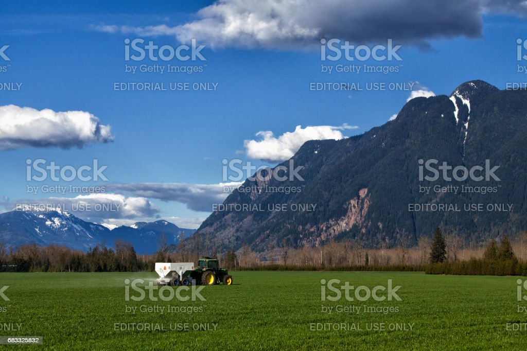 Tractor spraying fertilizer in field at Fraser Valley, BC, Canada royalty-free stock photo