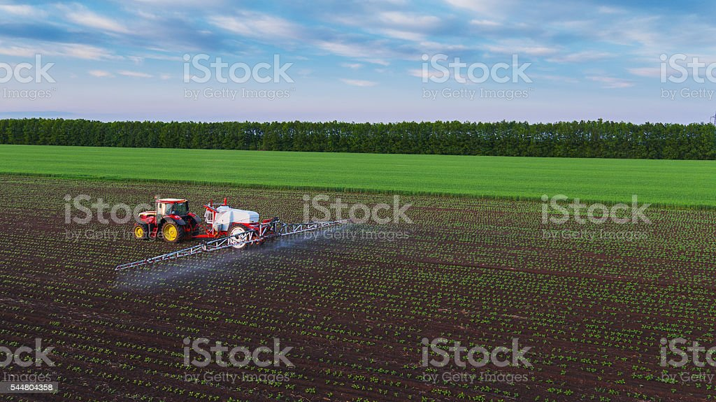 Tractor en el campo de la pulverización - foto de stock