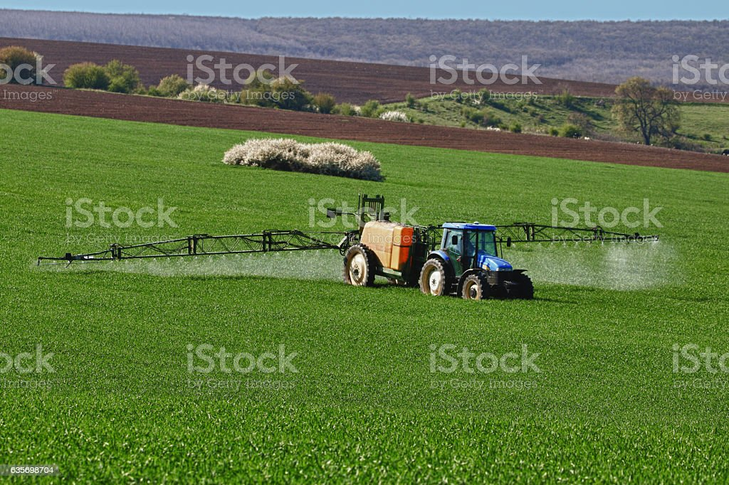 Tractor spraying field, rural landscape in countryside royalty-free stock photo