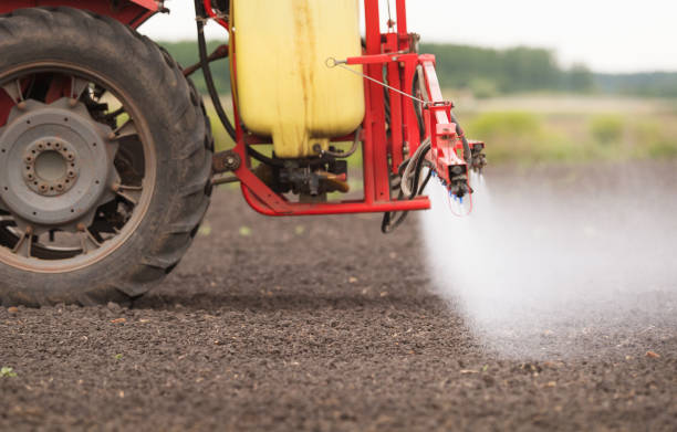 Tractor spraying pesticides on arable fields with sprayer Tractor spraying pesticides on arable fields with sprayer monoculture stock pictures, royalty-free photos & images