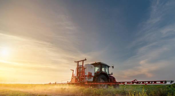 Traktor sprüht Pestizide auf Sojabohnenfeld mit Spritzer im Frühjahr – Foto