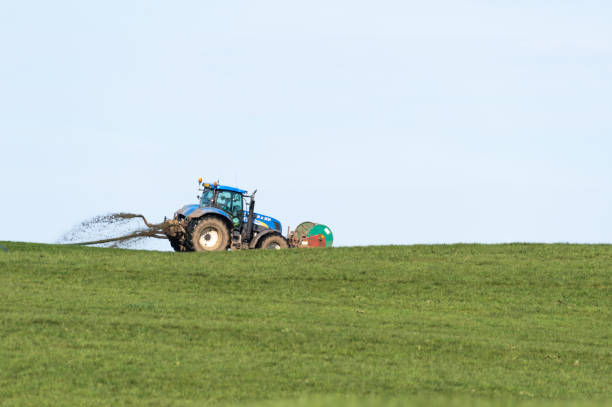 Tractor spraying slurry in a field on a spring day stock photo