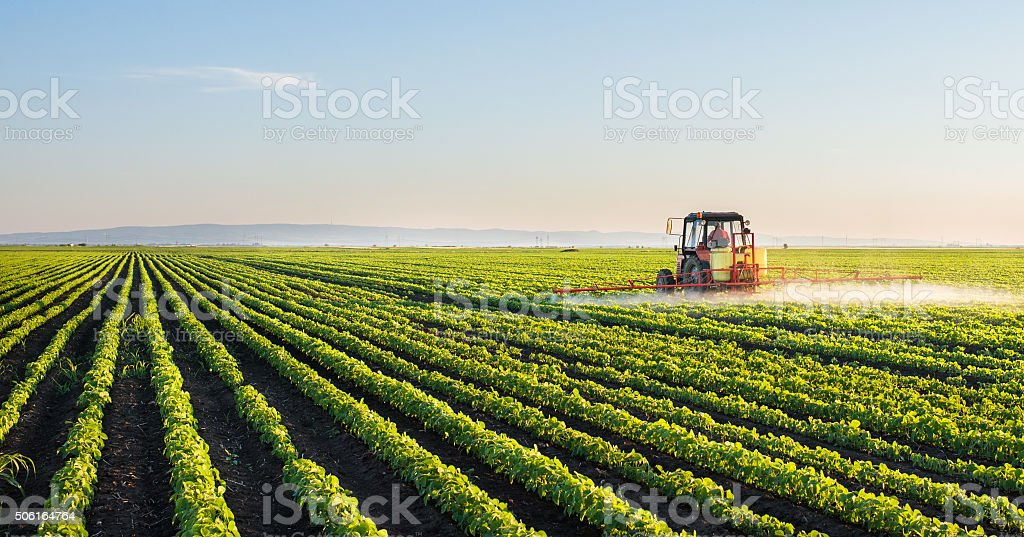 Tractor spraying soybean field - 免版稅商業金融與工業圖庫照片
