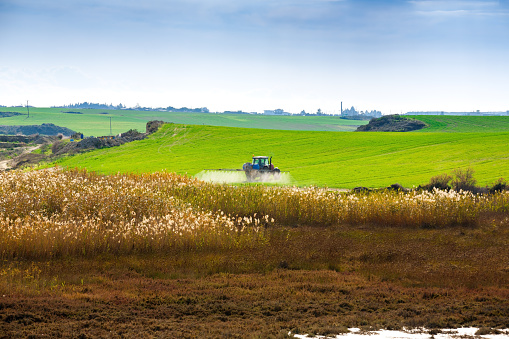 istock Tractor spraying the chemicals 1051421046
