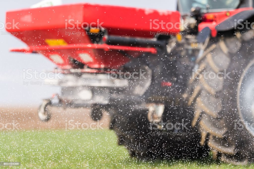 Tractor spreading artificial fertilizers  in field stock photo