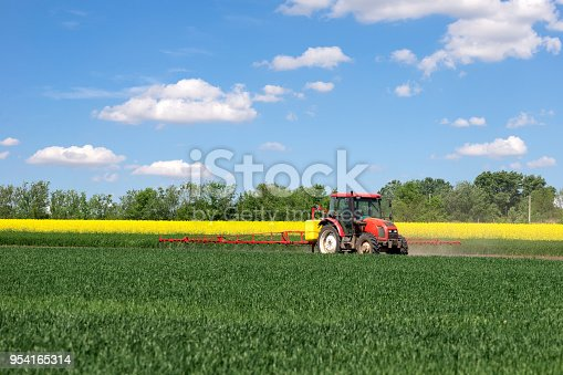 Tractor sprinkling pesticides on the agricultural field on a sunny spring day.