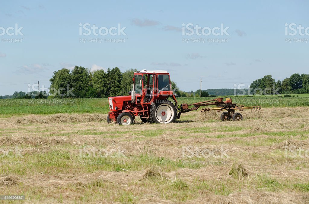 tractor ted hay dry grass in agriculture field stock photo