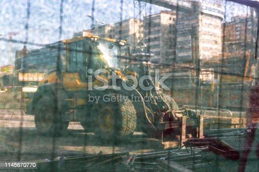 Tractor telescopic handler seen trough wind breaking fabric