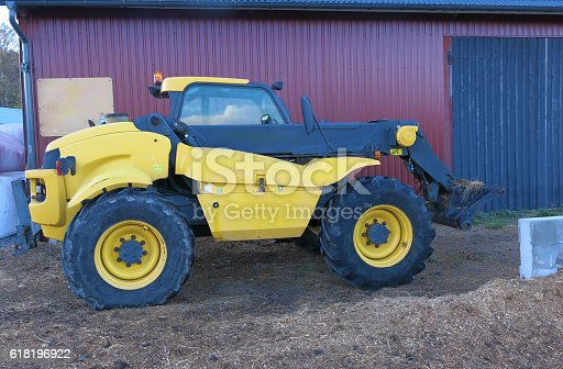 Tractor telescopic handler against a red barn