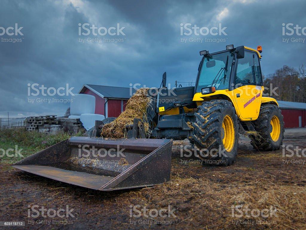 Tractor telescopic handler with bucket under dramatic sky scenery stock photo