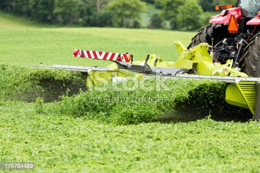A tractor towing a forage mower on an alfalfa (hay) field.