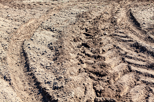 Tractor track on soil . Agricultural ground background
