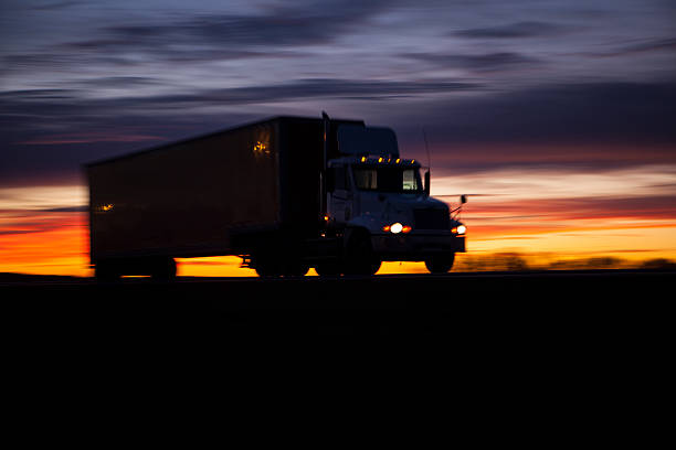 Tractor trailer on highway at sunset. stock photo