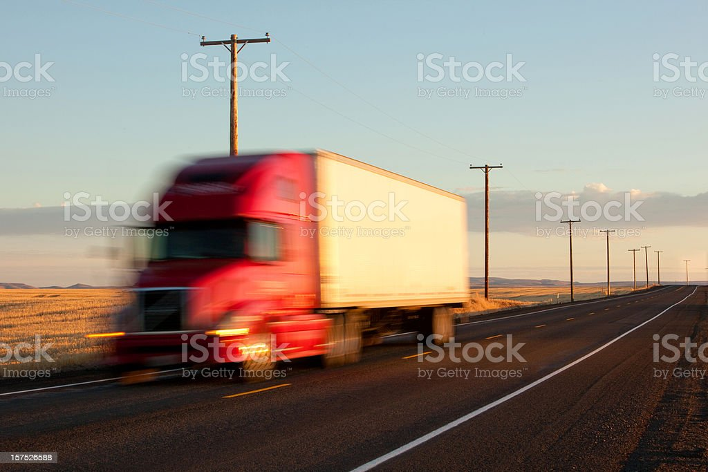 Tractor trailer speeds by at sunset royalty-free stock photo