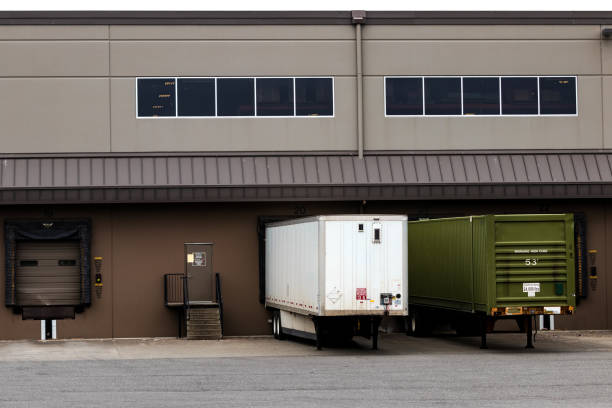 Tractor trailers at a warehouse cargo dock unloading stock photo