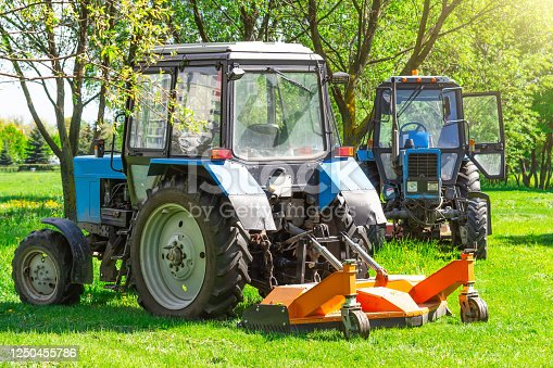 Tractor uses trailed lawn mower to mow grass on city lawns