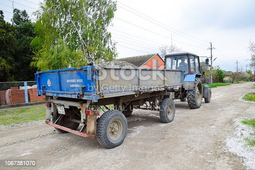 istock tractor with a rubble cart for repairing the road. Feeding holes on the road. Street repair. 1067381070