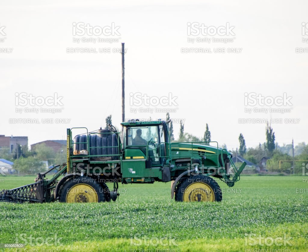 Tractor with a spray device for finely dispersed fertilizer. stock photo