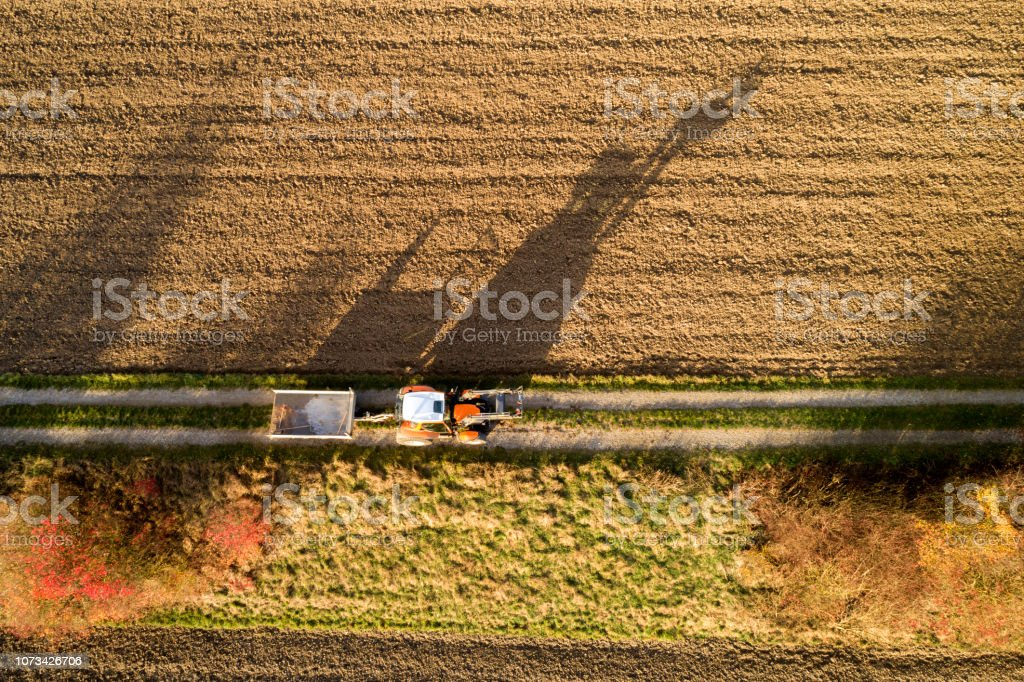 Aerial view of a tractor with a trailer on country road.