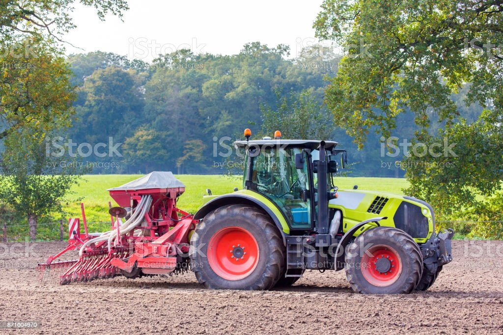 Tractor with agricultural machine on land stock photo