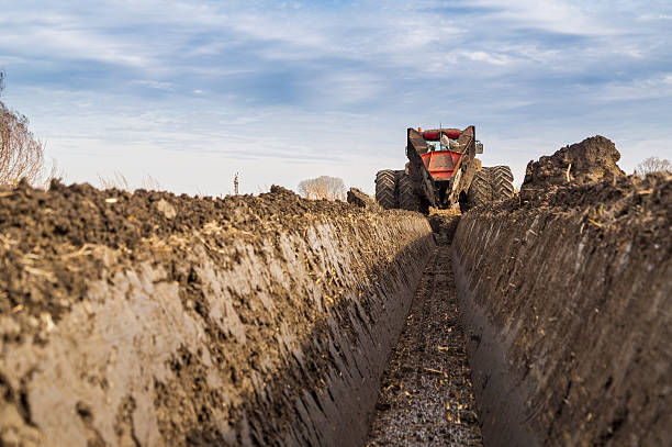 tractor with double wheeled ditcher digging drainage canal. - greppel stockfoto's en -beelden